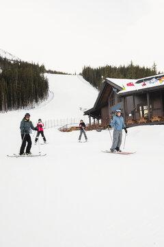 Skiers skiing ins now outside ski resort lodge