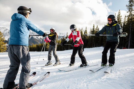 Instructor teaching skiers how to balance on snowy mountain ski slope