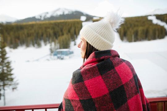 Female skier in knit hat and plaid blanket on ski resort balcony