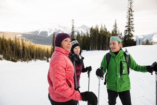 Friends snowshoeing and talking on snowy ski resort mountain