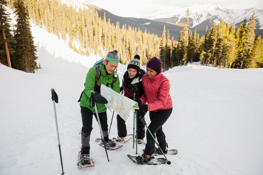Snowshoeing friends looking at map on snowy mountain ski slope