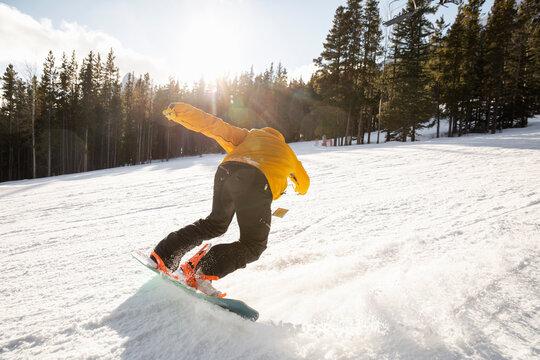 Man snowboarding on sunny snowy ski slope
