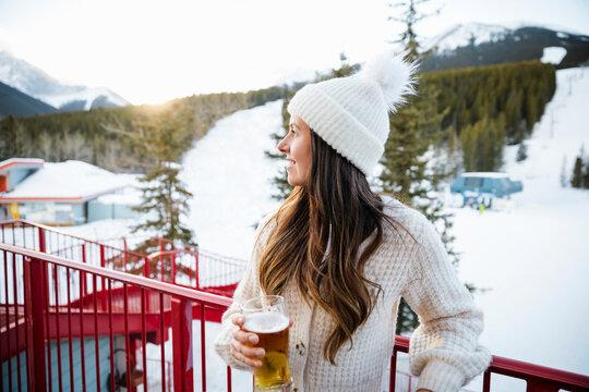 Portrait happy woman drinking beer on snowy ski resort balcony