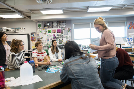 High school students discussing recycling project in science classroom