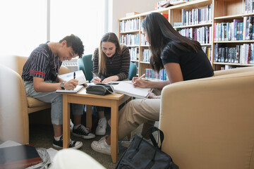 High school students studying and talking in library