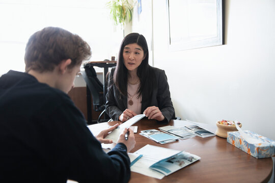 College counselor showing brochures to high school student in office