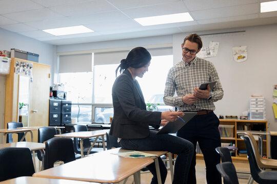 High school teachers with digital tablets talking in classroom