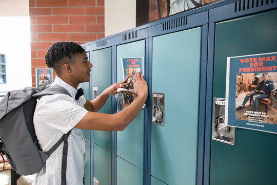 High school boy placing student government voting poster on lockers