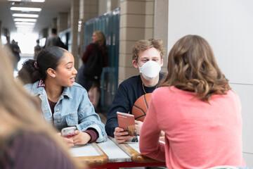 High school boy in flu mask talking with friends