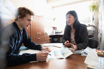Guidance counselor showing college brochures to high school student