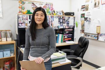 Portrait confident female high school teacher in classroom