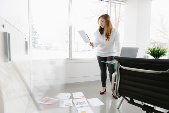 Woman reading document in modern office