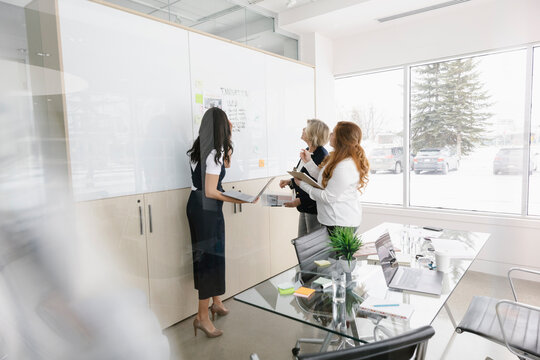 Three women discussing whiteboard in meeting