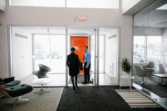 Security guard opening door for businesswoman