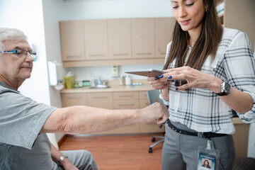 Doctor with digital tablet photographing hand of senior patient