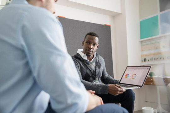 Two men using laptop in modern office