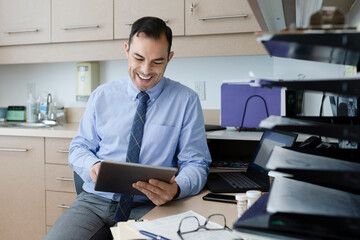 Smiling male doctor using digital tablet in clinic exam room