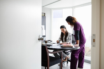 Female doctor and nurse meeting at desk in office