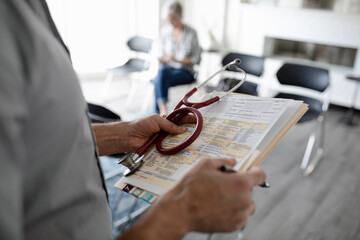Close up doctor with stethoscope and medical chart in clinic