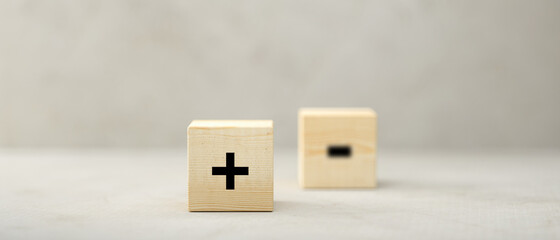 cubes with PLUS symbol in focus and MINUS out of focus on paper surface in front of concrete...