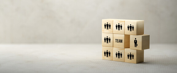 cubes with people symbols and the word TEAM on paper surface in front of concrete background