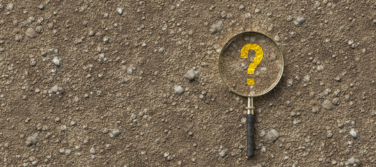 magnifying glass with question mark on dirt gravel background