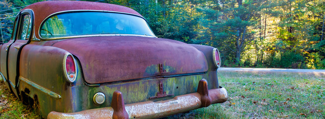 Old abandoned vintage car on the grass in foliage season