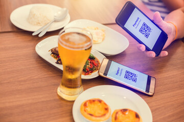 Hand using smart phone to scan QR code tag with blurry food, dessert and beer in restaurant to...