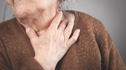 Elderly woman touching the neck feeling sore throat pain.