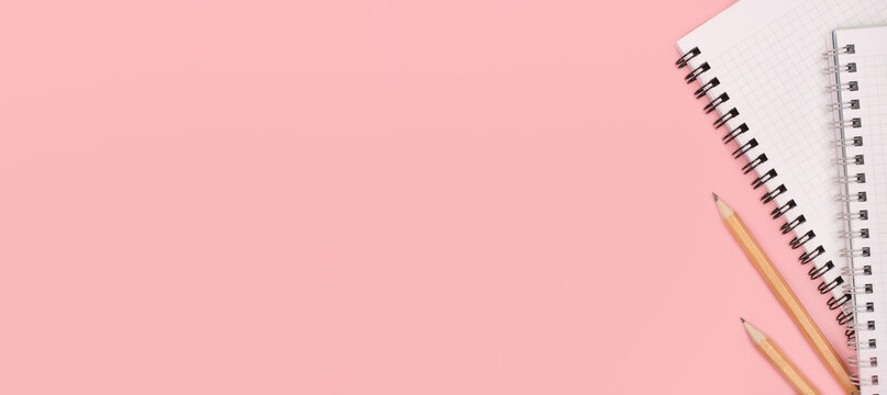 Notepad and pencils on a pink panoramic background. Copy space. Stationery. Back to school concept. Top view and flat lay.