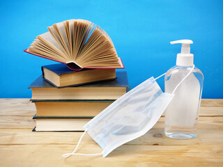 Back To School Coronavirus Covid-19, book pile, sanitizer and medical mask
