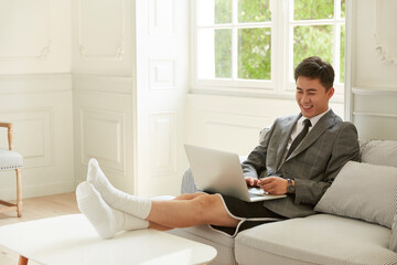 young asian corporate executive working from home video chatting using laptop