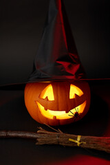 halloween and holiday decorations concept - jack-o-lantern in witch's hat with spider and broom in darkness