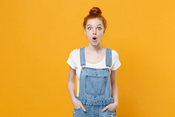 Shocked young readhead girl in casual denim clothes white t-shirt isolated on yellow background...