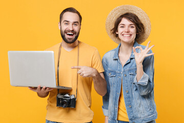 Funny tourists couple friends guy girl isolated on yellow background. Passenger traveling abroad on...