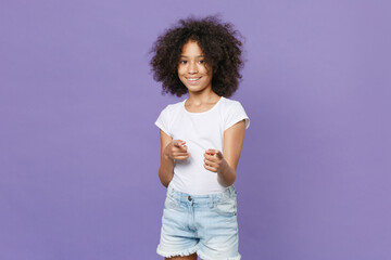 Smiling little african american kid girl 12-13 years old in white t-shirt isolated on violet...