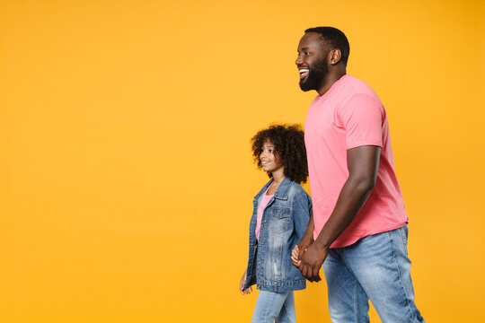 Side view of funny african american guy girl brother sister in denim pink clothes isolated on yellow wall background studio. People lifestyle concept. Mock up copy space. Holding hands, walking going.