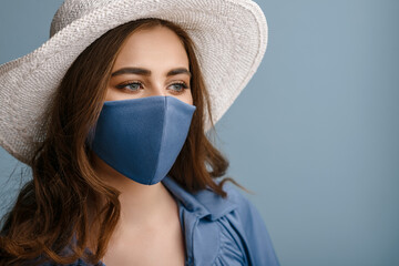 Woman wearing stylish protective face mask, posing on blue background. Trendy Fashion accessory...