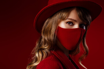 Woman wearing stylish protective red face mask, hat, coat, posing on red background. Trendy Fashion...