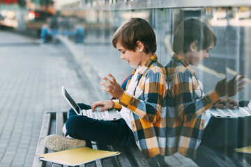 A happy boy is sitting on a bench, holding a laptop on his lap. The boy communicates with friends using the computer, waving to them. Education, technology, distance learning