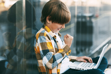A happy boy in a plaid shirt sits on a bench and holds a laptop in his lap. The boy communicates with friends on the Internet. Social distance, positive emotions. Education, technology