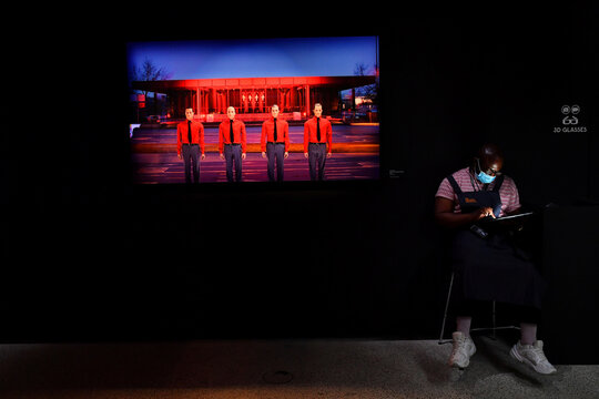 A gallery assistant sits during the opening of  'Electronic: From Kraftwerk to The Chemical Brothers' in London