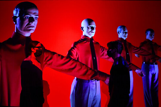 Gallery assistants pose for the media during  the opening of  'Electronic: From Kraftwerk to The Chemical Brothers' in London