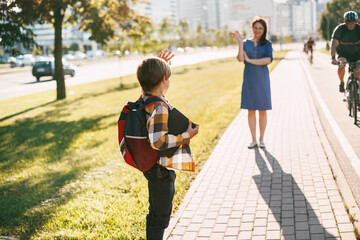 A mother walks her son to school. Mom Waves goodbye to the boy, and he waves back. The concept of training and education, a place for text