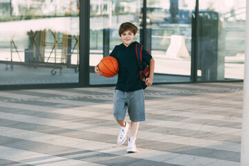 A cheerful boy with a backpack and a basketball. A boy hurries to basketball practice. Training, education, physical education