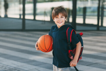 Portrait of a beautiful boy in sports uniform with a backpack and a basketball. The boy smiles and holds the ball in his hands. Training, education, physical education