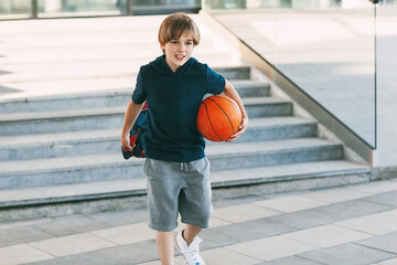A cute boy with a backpack in one hand and a basketball in the other. The boy in shape in a hurry for a workout but basketball. Training, education, physical education