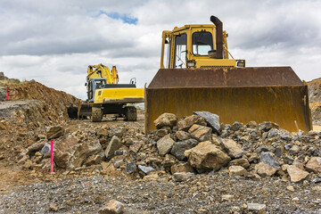 Excavator doing construction work on a road, moving stone and rock