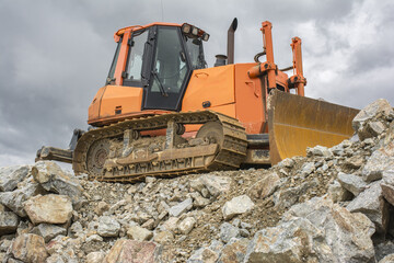 Excavator and heavy machinery for processing rock and stone in a quarry