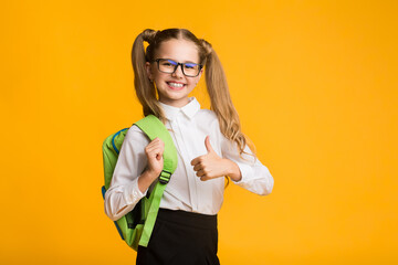 Happy Elementary Student Girl Gesturing Thumbs-Up Posing Over Yellow Background
